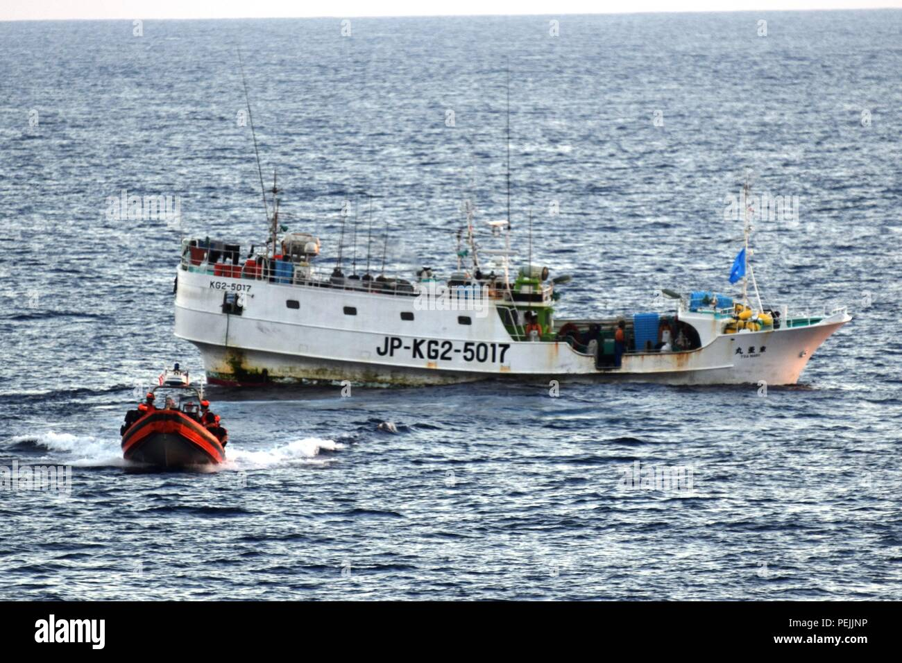 A Coast Guard Cutter Sequoia (WLB 215) boarding team along with an Federated States of Micronesia National Police shiprider return from boarding a 48-foot Japanese-flagged long line fishing vessel operating inside the FSM exclusive economic zone, August 2015. Patrolling the FSM EEZ, Sequoia travelled over 4,068 miles and conducted 10 law enforcement boardings, as well as providing deterrence for illegal fishing activity and strengthening international partnerships. All boardings were conducted under the FSM-U.S. Bilateral Agreement. (U.S. Coast Guard photo by Lt. Jeffrey West/Released) - Stock Image