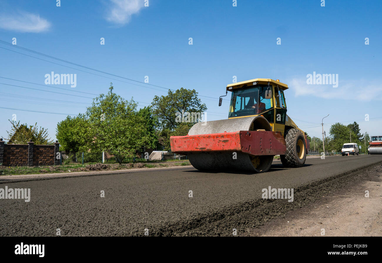 Heavy Vibration roller at asphalt pavement working on the new road construction site. Repairing - Stock Image
