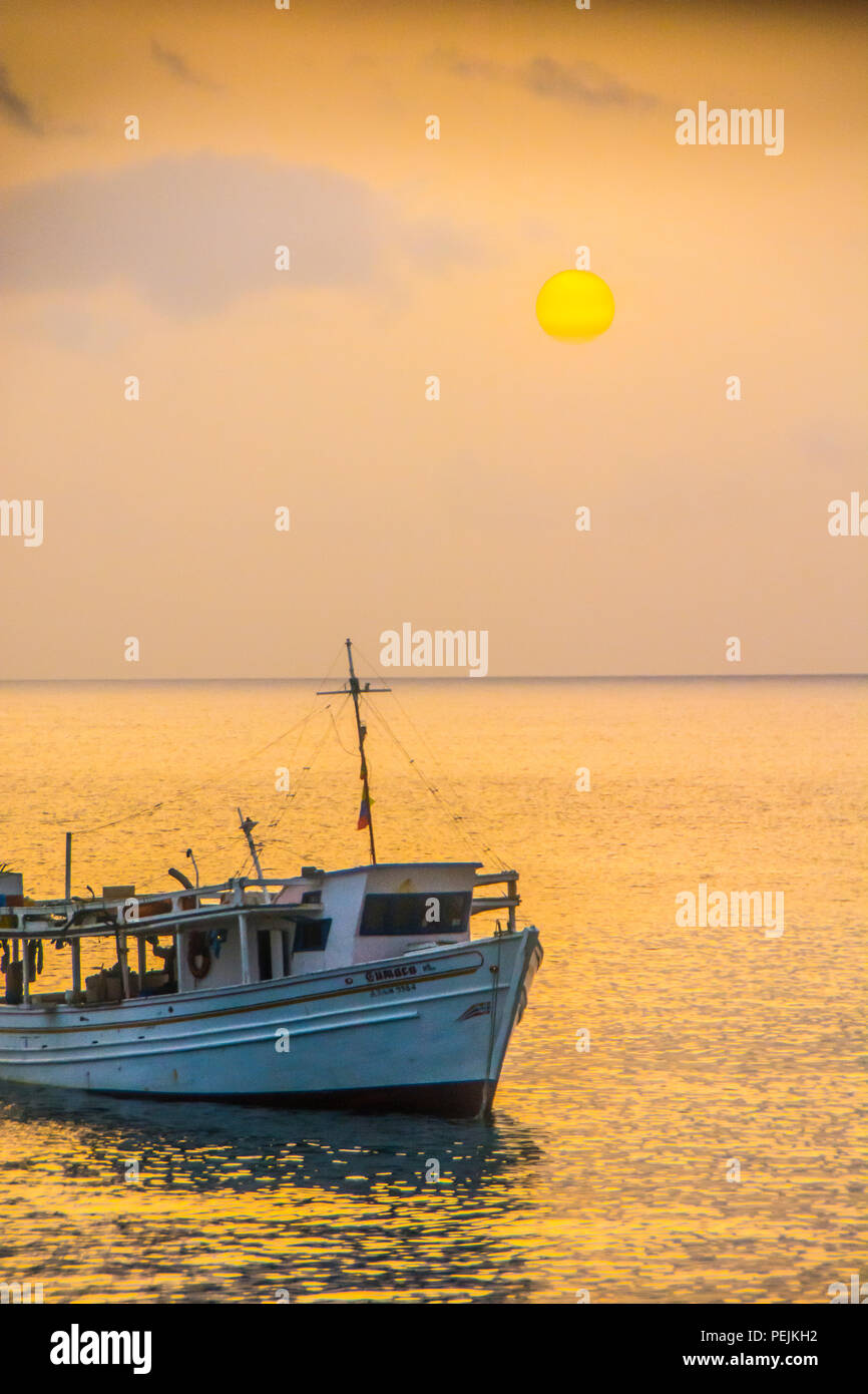 A boat at anchor off the coast of the island of Grenada Stock Photo