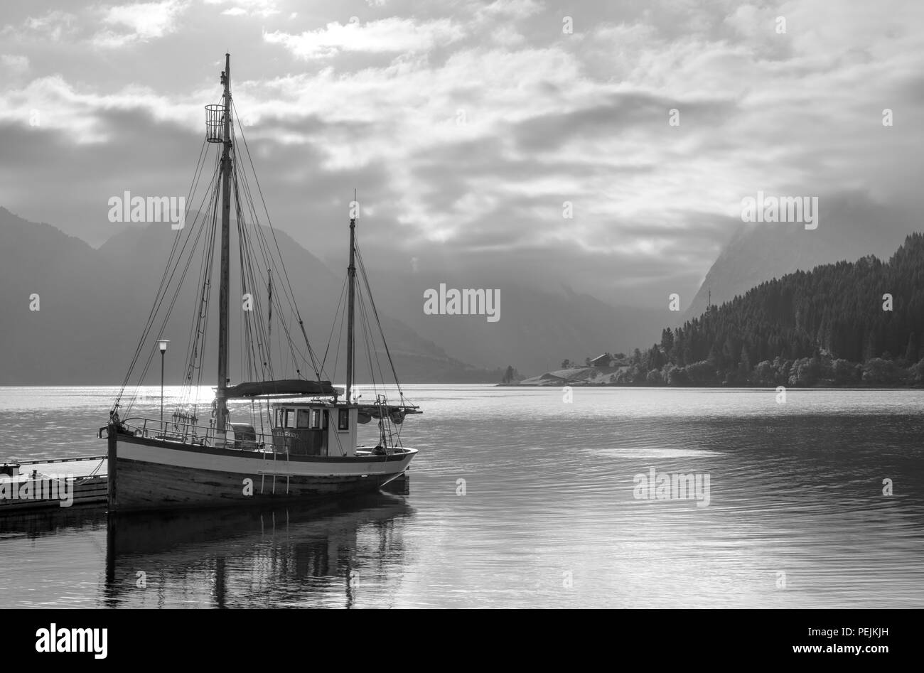 Norway fjords. Boat moored at a jetty outside the Sagafjord Hotel in the early morning, Sæbø, Hjørundfjorden, Møre og Romsdal, Norway - Stock Image