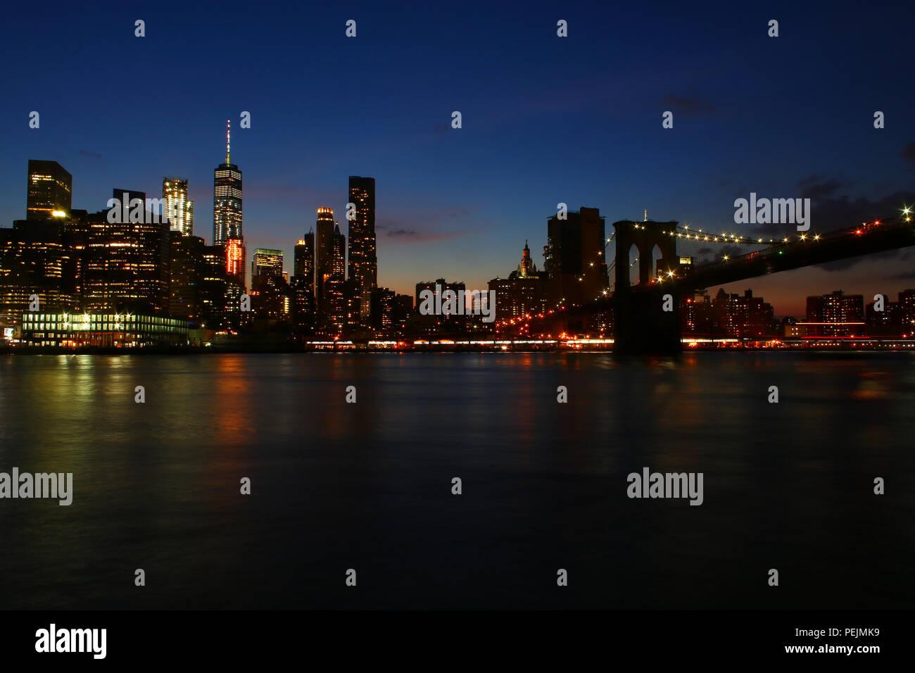 NEW YORK, NY - JULY 03: Financial District, Lower Manhattan, and Brooklyn Bridge skyline after sunset as seen from Brooklyn Bridge Park, Brooklyn on J Stock Photo