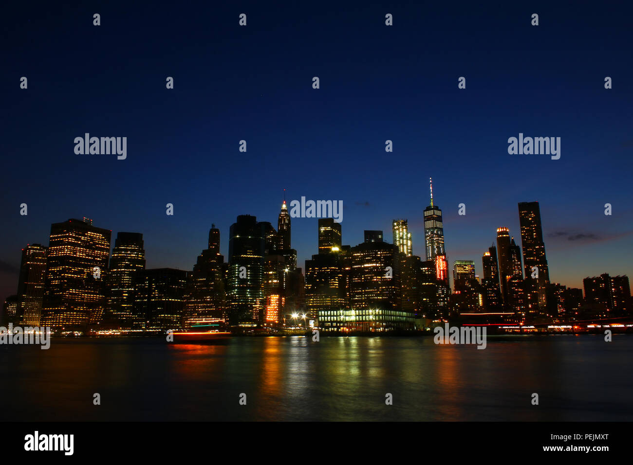 NEW YORK, NY - JULY 03: Financial District, Lower Manhattan skyline after sunset as seen from Brooklyn Bridge Park, Brooklyn Stock Photo