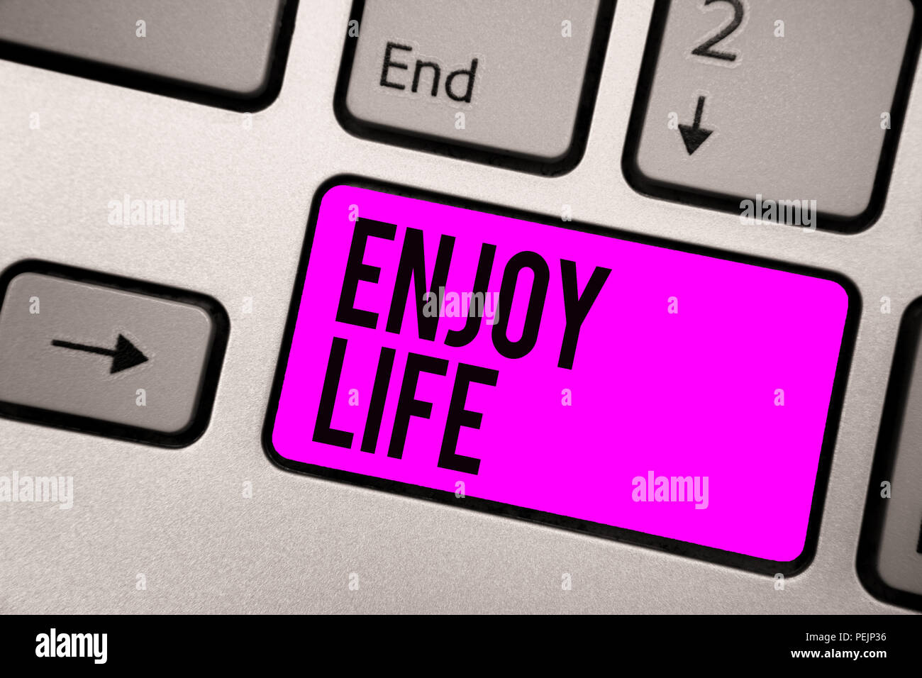 Text sign showing Enjoy Life. Conceptual photo Any thing, place,food or person, that makes you relax and happy Keyboard purple key Intention create co - Stock Image