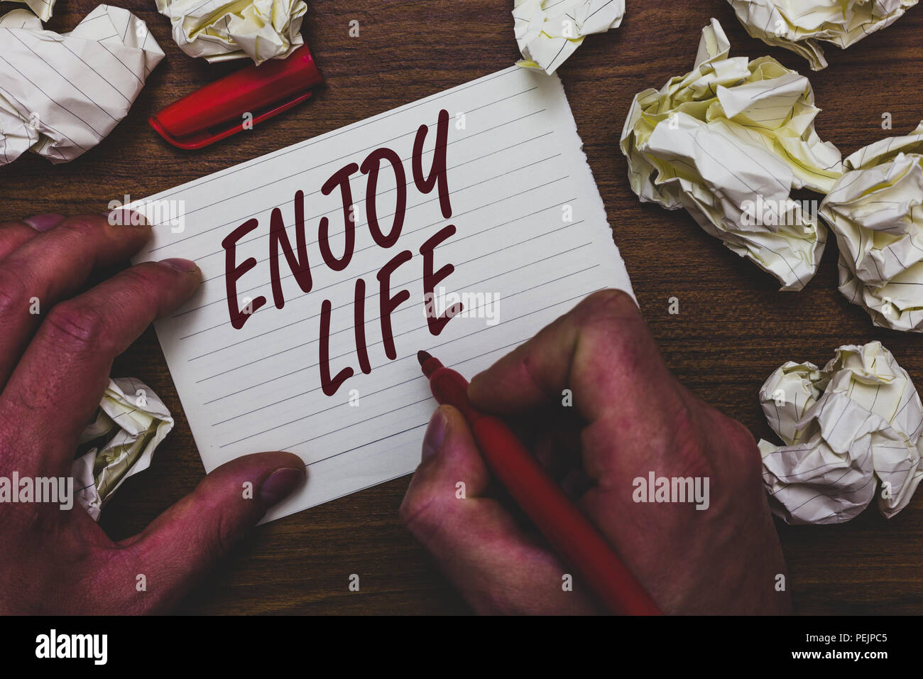 Handwriting text writing Enjoy Life. Concept meaning Any thing, place,food or person, that makes you relax and happy Man holding marker notebook page  - Stock Image