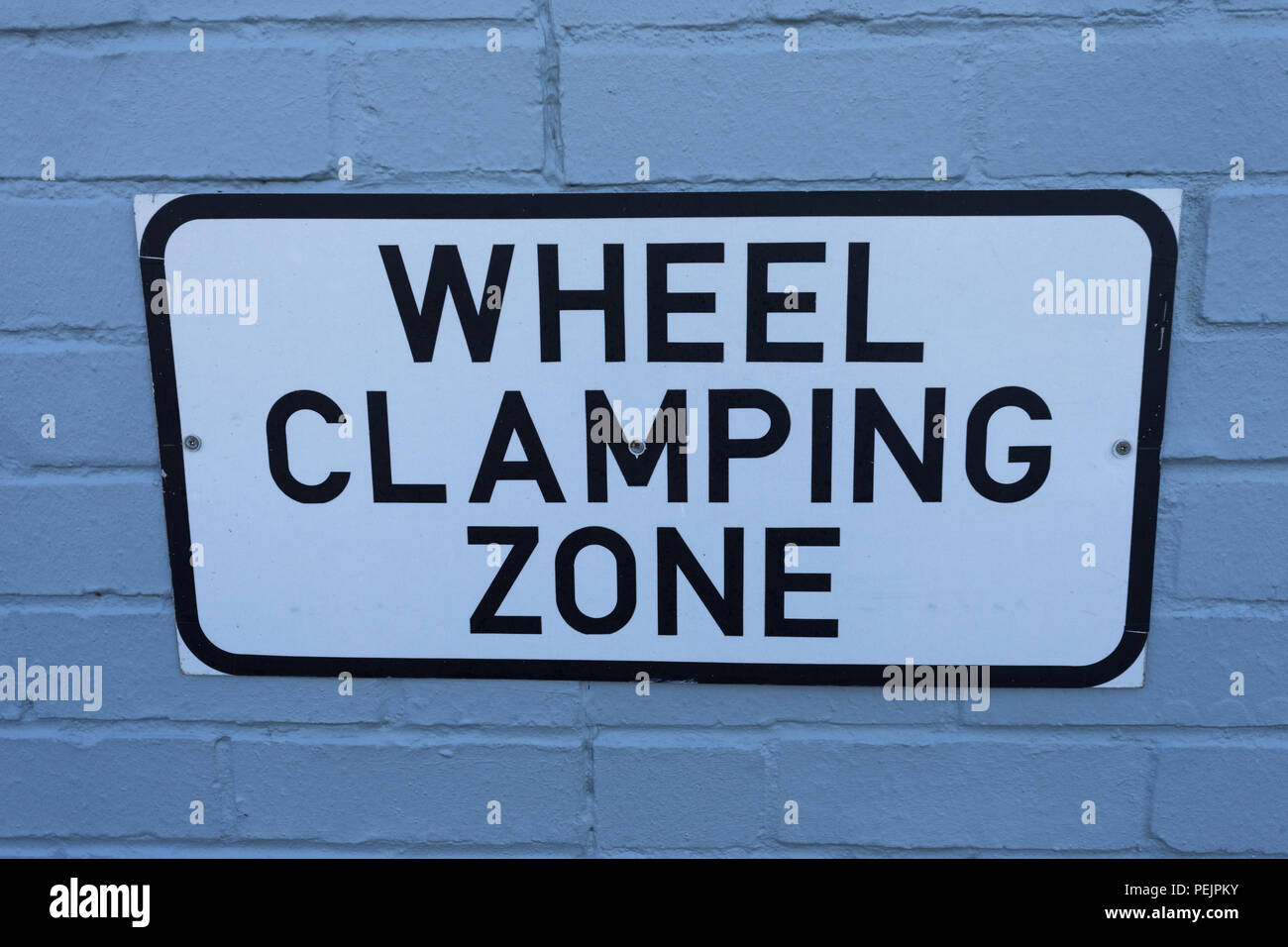 sign for wheel clamping zone on wall in city - Stock Image