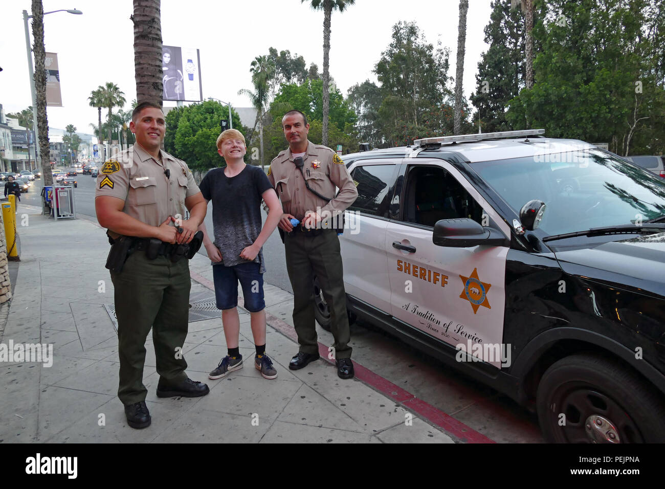 Boy poses with two police officers in Los Angeles California U.S.A. - Stock Image