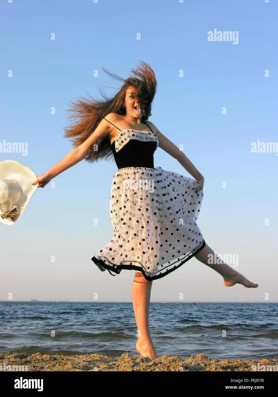 cheerful young woman at the beach, windy weather, motion blur - Stock Image