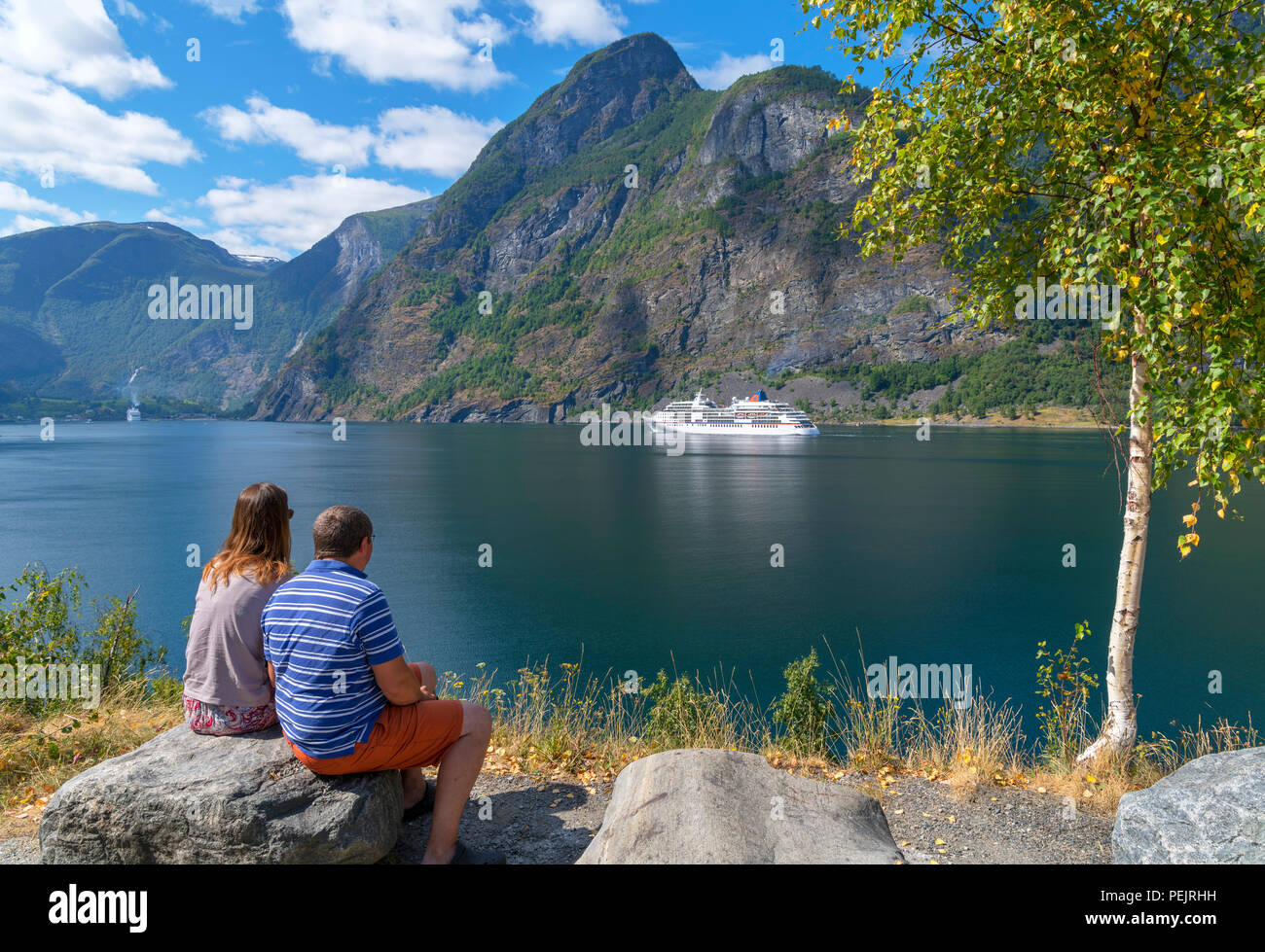 Couple watching a cruise ship sailing into Flåm, Aurlandsfjord, Sognefjord, Sogn og Fjordane, Norway - Stock Image