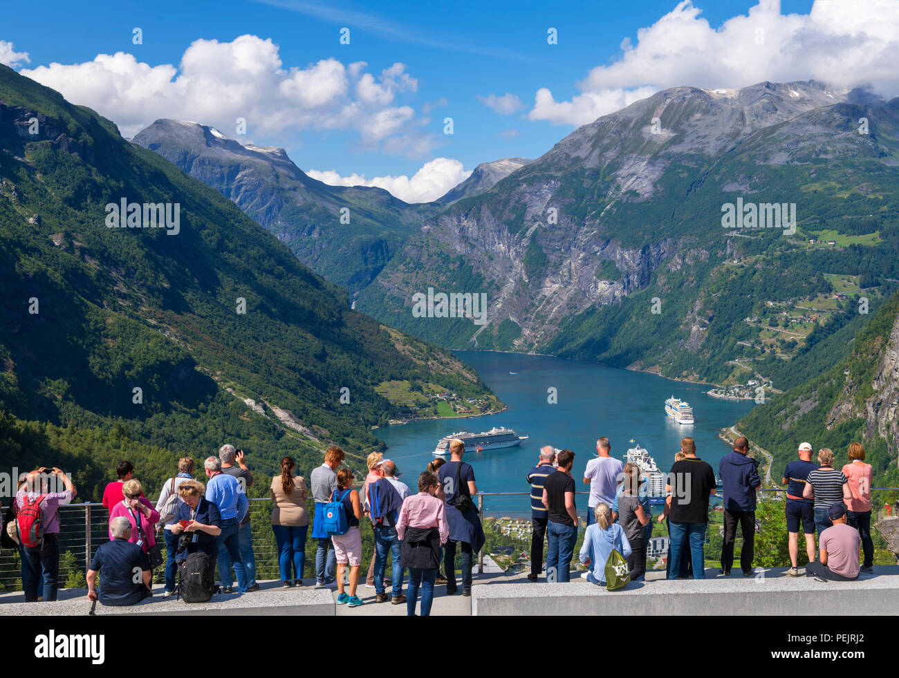 Geiranger, Norway. Tourists at the viewpoint overlooking the town of Geiranger and Geirangerfjord, Norway - Stock Image