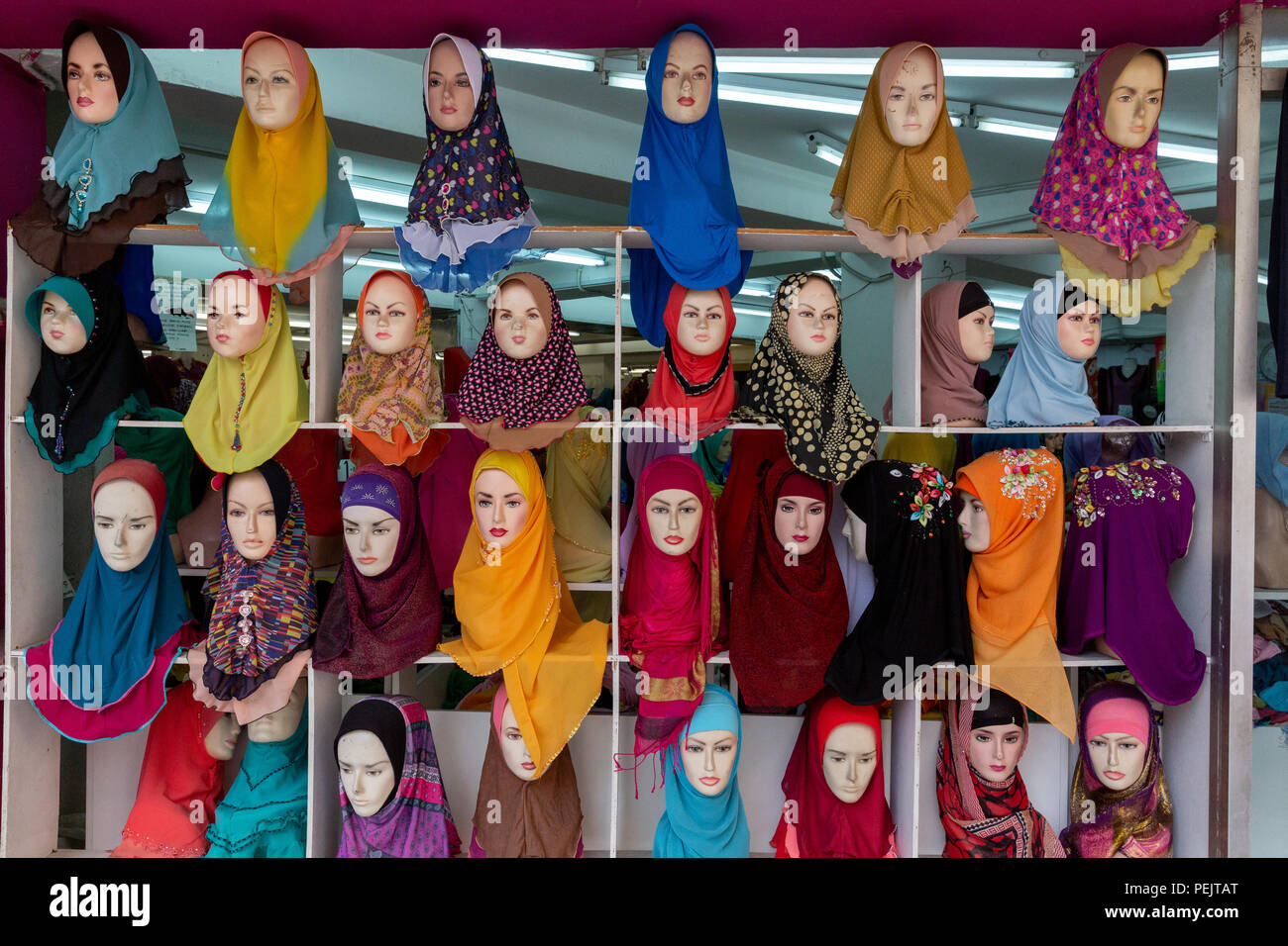 Headscarves (aka hijabs or tudungs) on mannequin heads in front of a store in Kuala Lumpur, Malaysia. - Stock Image