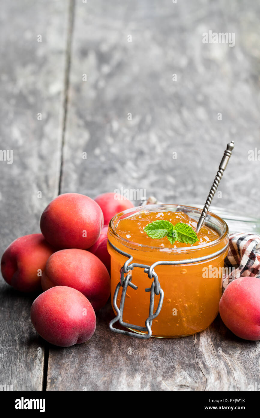 Red apricot  jam with caramel in a clear glass jar on wooden table - Stock Image