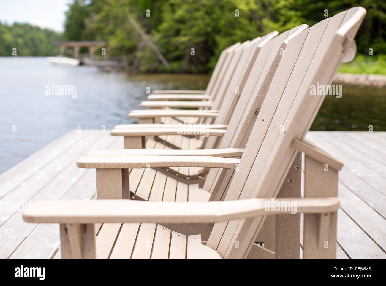 Side view of Muskoka chairs on a dock. - Stock Image
