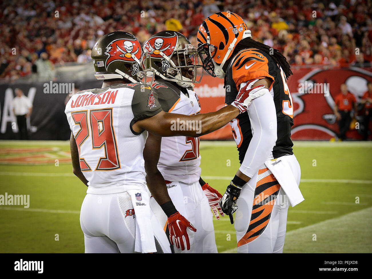 Tampa Bay Buccaneers cornerback Leonard Johnson and safety Keith Tandy confront Cincinnati Bengals linebacker Emmanuel Lamur during an NFL preseason Buccaneers vs. Bengals football game, Aug. 24, 2015, in Tampa, Fla. The game featured a salute to military service, which included a U.S. Special Operations Command Para-Commandos parachute demonstration and a U.S. Coast Guard HC-130J Hercules fly-over. (U.S. Air Force photo by Tech. Sgt. Brandon Shapiro) Stock Photo