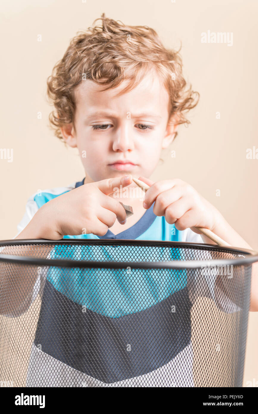 Concept of back to school. Child sharpening a pencil next to a wastepaper basket. - Stock Image