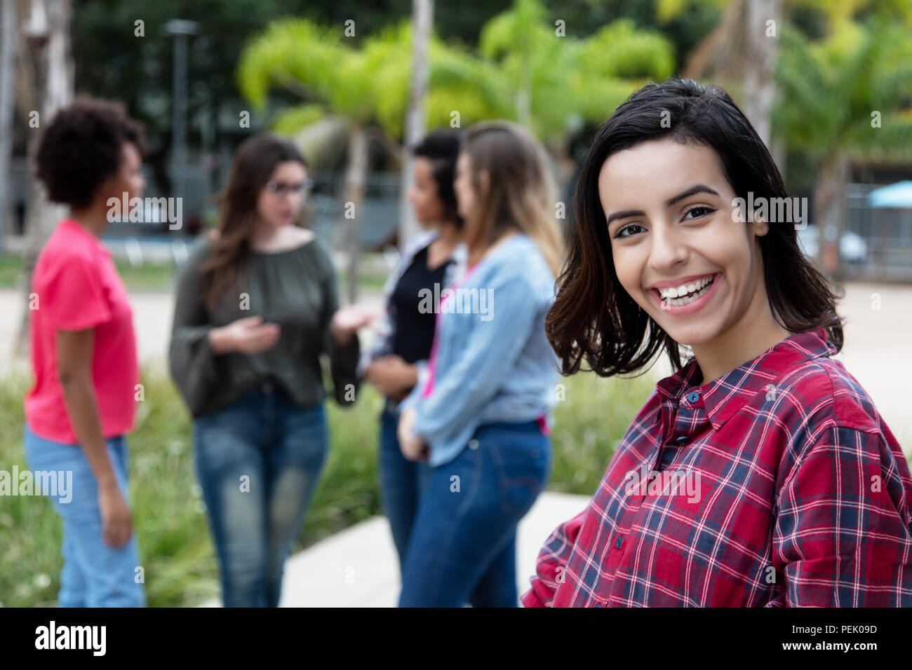 Laughing mexican young adult woman with girlfriends outdoors in the summer in the city - Stock Image