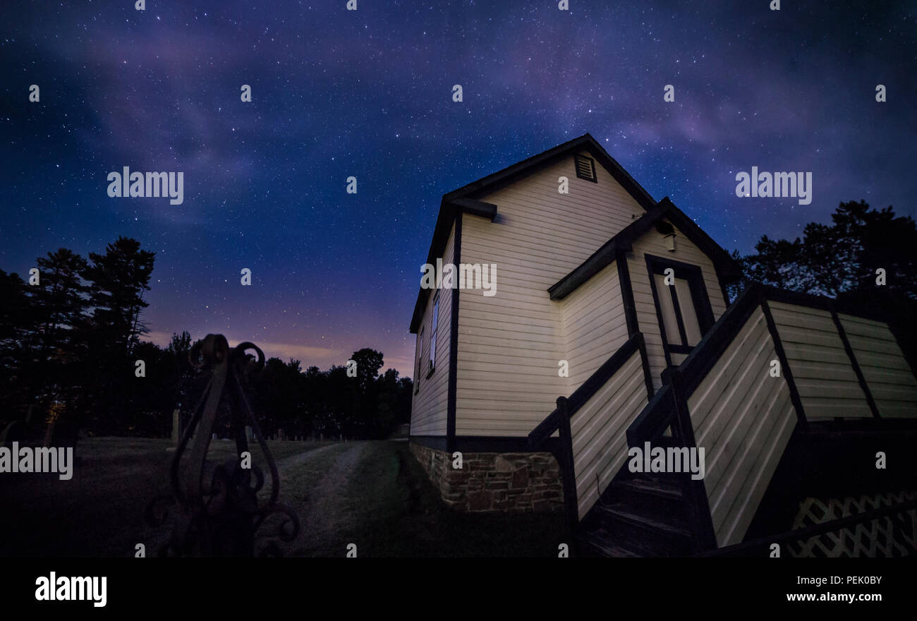 A country church beside a graveyard at night. - Stock Image