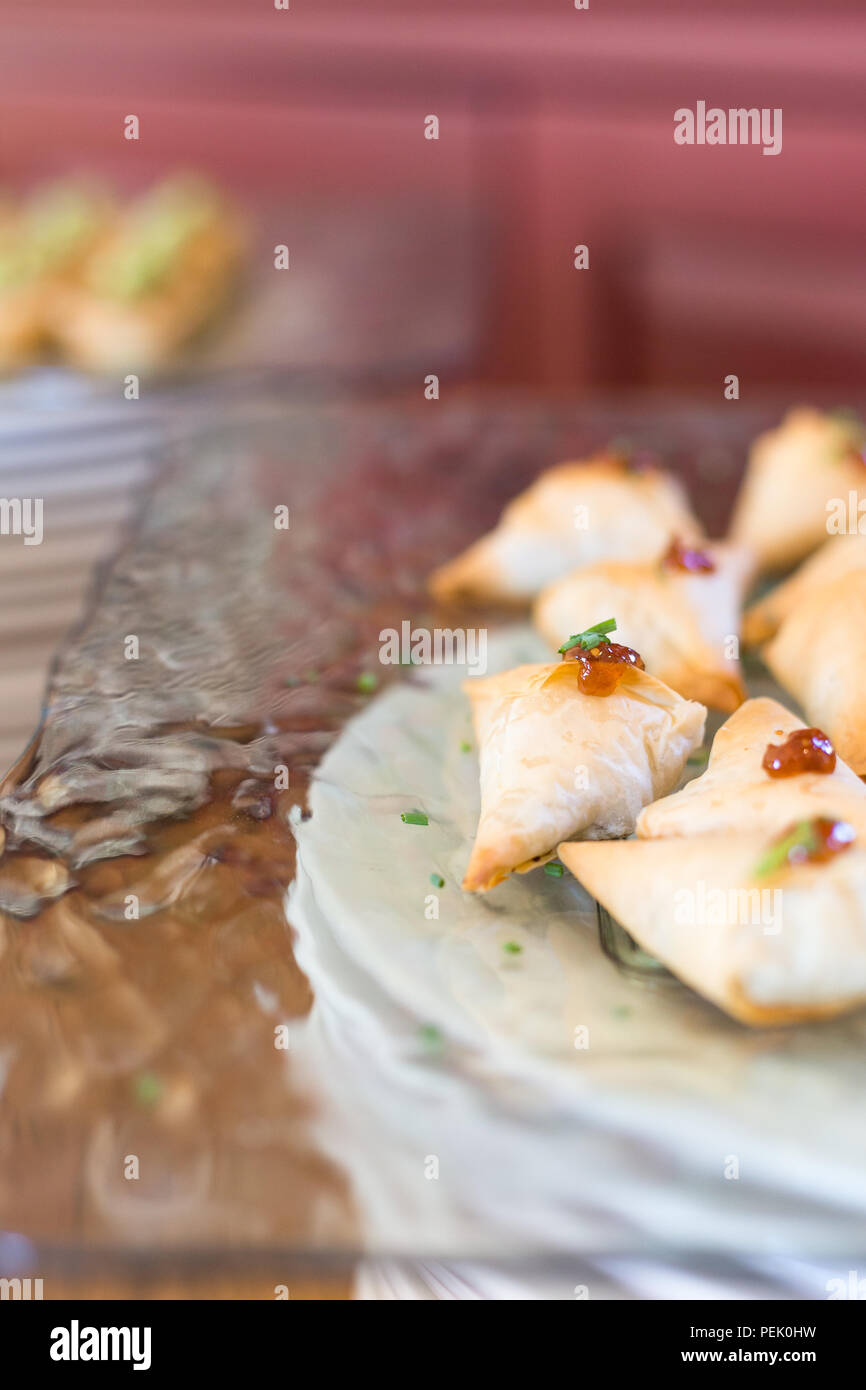 Filo pastry parcels on a glass plate. - Stock Image