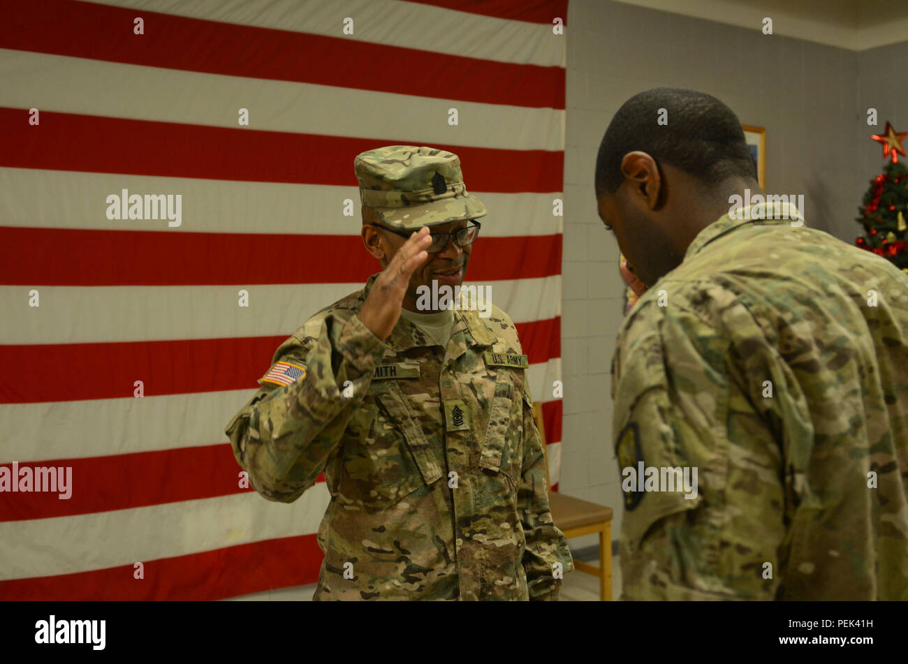 Newly promoted Sgt. Maj. Bryan Smith, the operations noncommissioned officer in charge of 149th Human Resource Texas Army National Guard, originally from Freeport, Texas, salutes Capt. Joseph Taylor, the commander of Task Force Warhammer, originally from Richmond, Va., after Capt. Taylor places the SGM patrol cap on SGM Smith during his promotion ceremony at Mihail Kogălniceanu Air Force Base, Romania, Dec. 10, 2015. (U.S. Army Photo by Staff Sgt. Steven M. Colvin/Released) - Stock Image