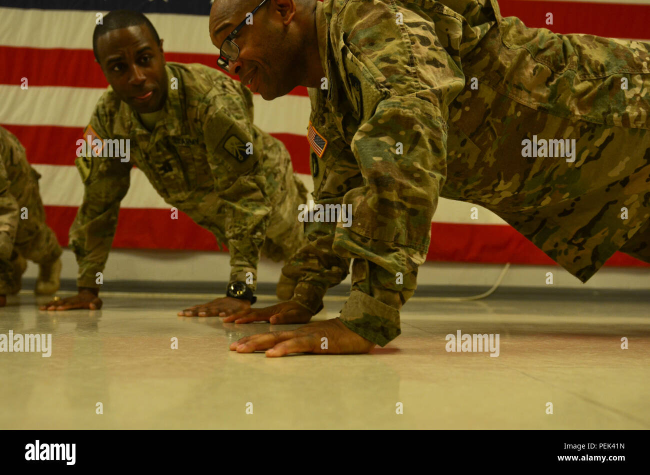 Newly promoted Sgt. Maj. Bryan Smith, the operations noncommissioned officer in charge of 149th Human Resource Texas Army National Guard, originally from Freeport, Texas, along with some Soldiers and officers, conducts in-cadence pushups during his promotion ceremony at Mihail Kogălniceanu Air Force Base, Romania, Dec. 10, 2015. (U.S. Army Photo by Staff Sgt. Steven M. Colvin/Released) - Stock Image