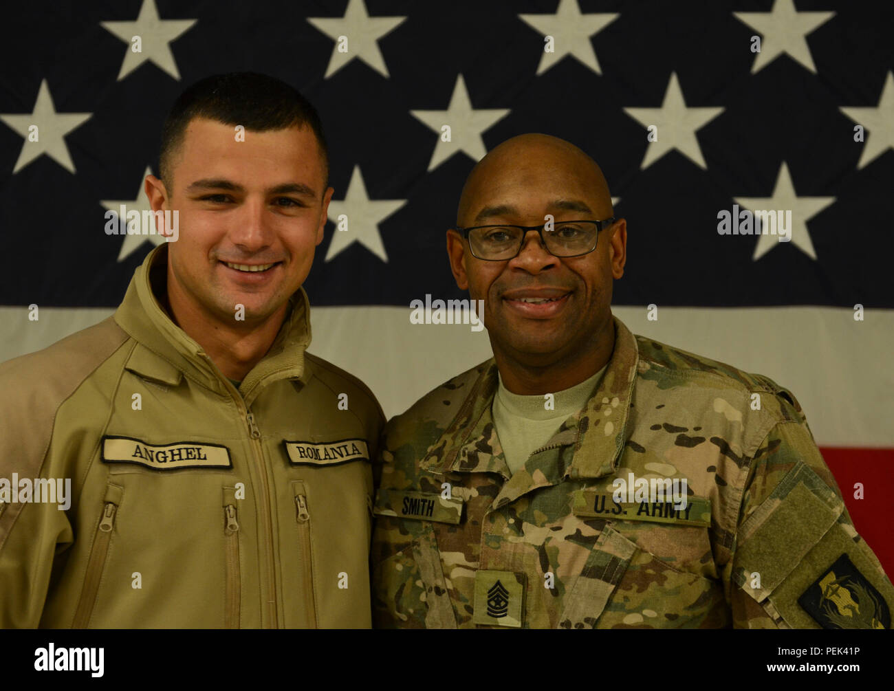 Newly promoted Sgt. Maj. Bryan Smith, the operations noncommissioned officer in charge of 149th Human Resource Texas Army National Guard, originally from Freeport, Texas, poses for a photo with his Romanian Army friend, Sgt. Laurentiu Anghel, during his promotion ceremony at Mihail Kogălniceanu Air Force Base, Romania, Dec. 10, 2015. (U.S. Army Photo by Staff Sgt. Steven M. Colvin/Released) - Stock Image
