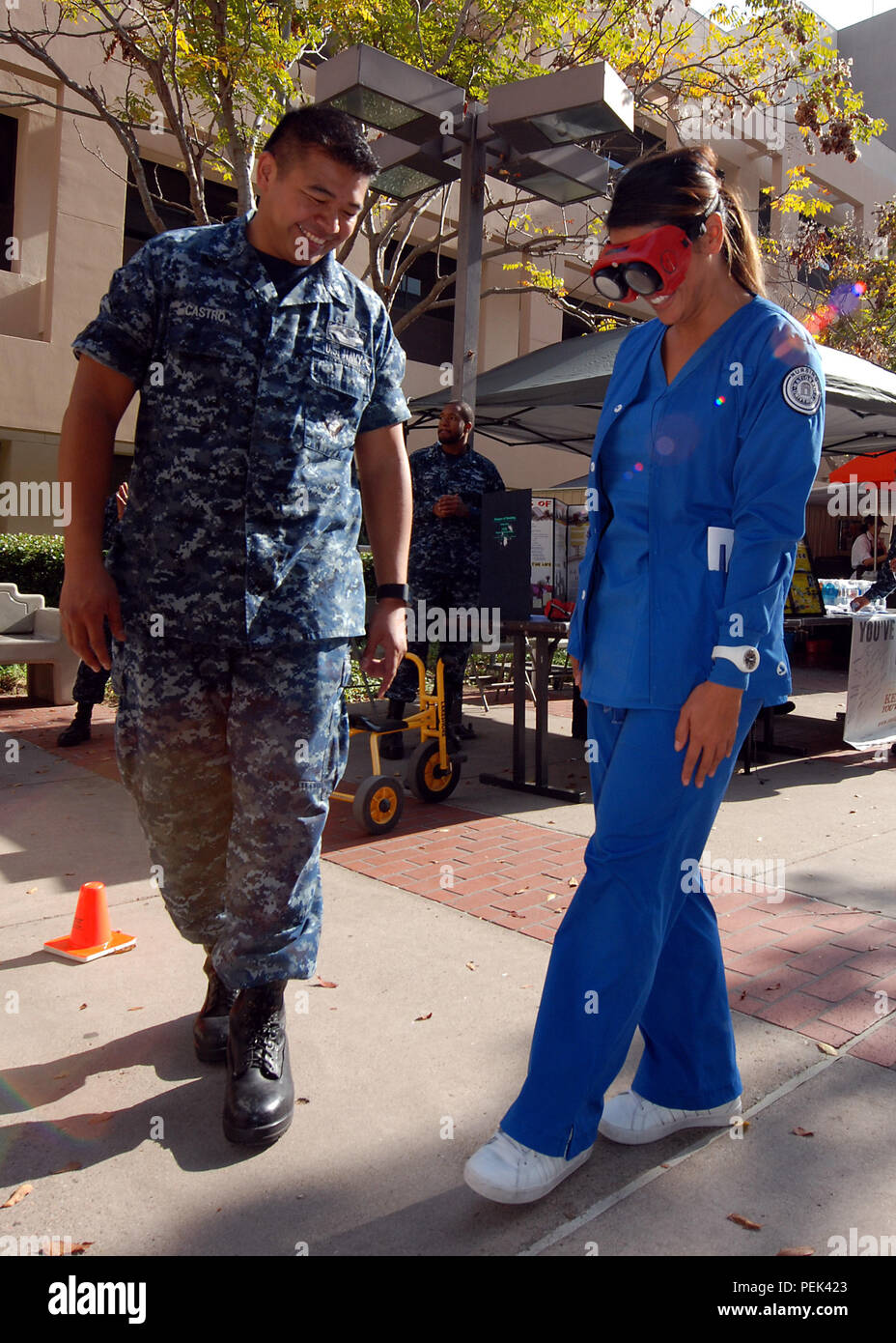 151210-N-BB534-001 SAN DIEGO (Dec. 10, 2015) Hospital Corpsman 2nd Class Anjo Castro supervises student nurse Cindy Nguyen walking a straight line while wearing vision impairment goggles, simulating a blood alcohol level of .08 percent, at Naval Medical Center San Diego (NMCSD) Dec. 10, 2015. The NMCSD Drug and Alcohol Program adviser team set up the interactive display for staff and patients as part of the Keep What You've Earned campaign. (U.S. Navy photo by Mass Communication Specialist 1st Class Elizabeth Merriam) - Stock Image