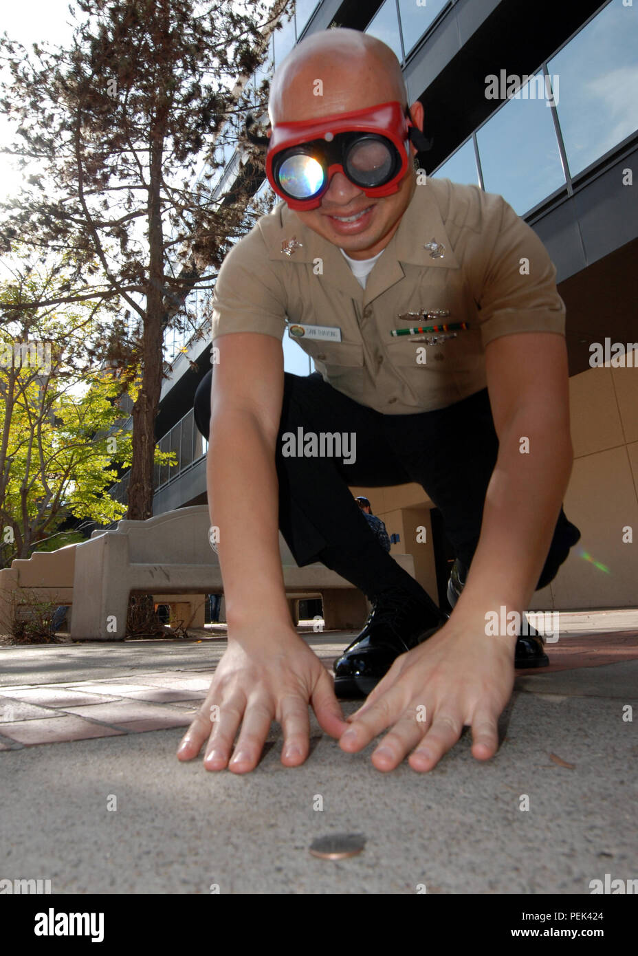 151210-N-BB534-002 SAN DIEGO (Dec. 10, 2015) Hospital Corpsman 1st Class Soutsakhone Sanethavong attempts to pick up a quarter while wearing vision impairment goggles, simulating a blood alcohol level of .08 percent, at Naval Medical Center San Diego(NMCSD) Dec. 10 2015. The NMCSD Drug and Alcohol Program adviser team set up the interactive display for staff and patients as part of the Keep What You've Earned campaign. (U.S. Navy photo by Mass Communication Specialist 1st Class Elizabeth Merriam) - Stock Image