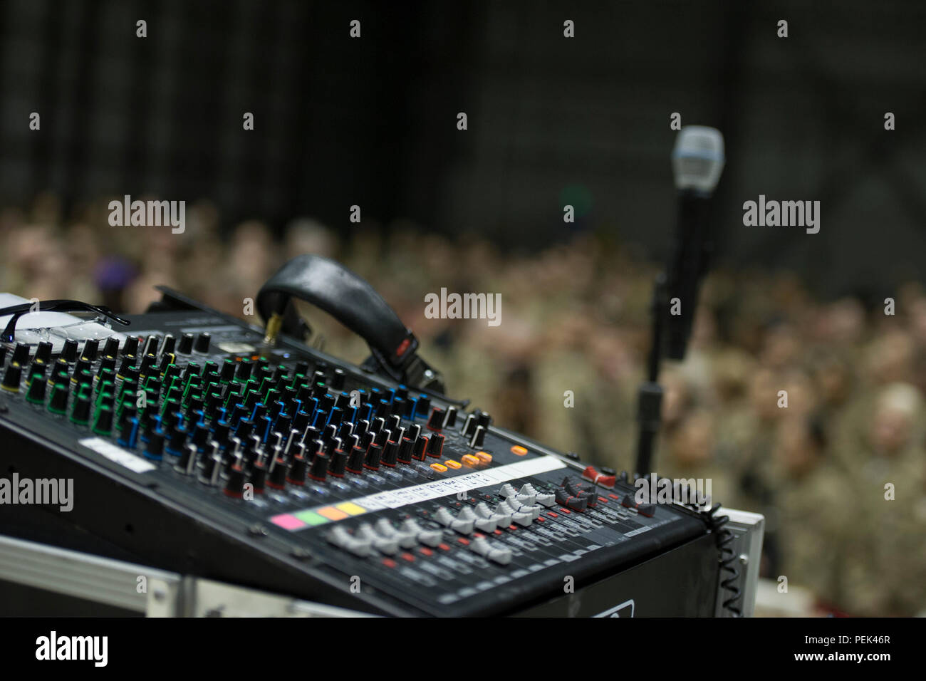 Sound equipment sits on stage as a crowd of service members fills a