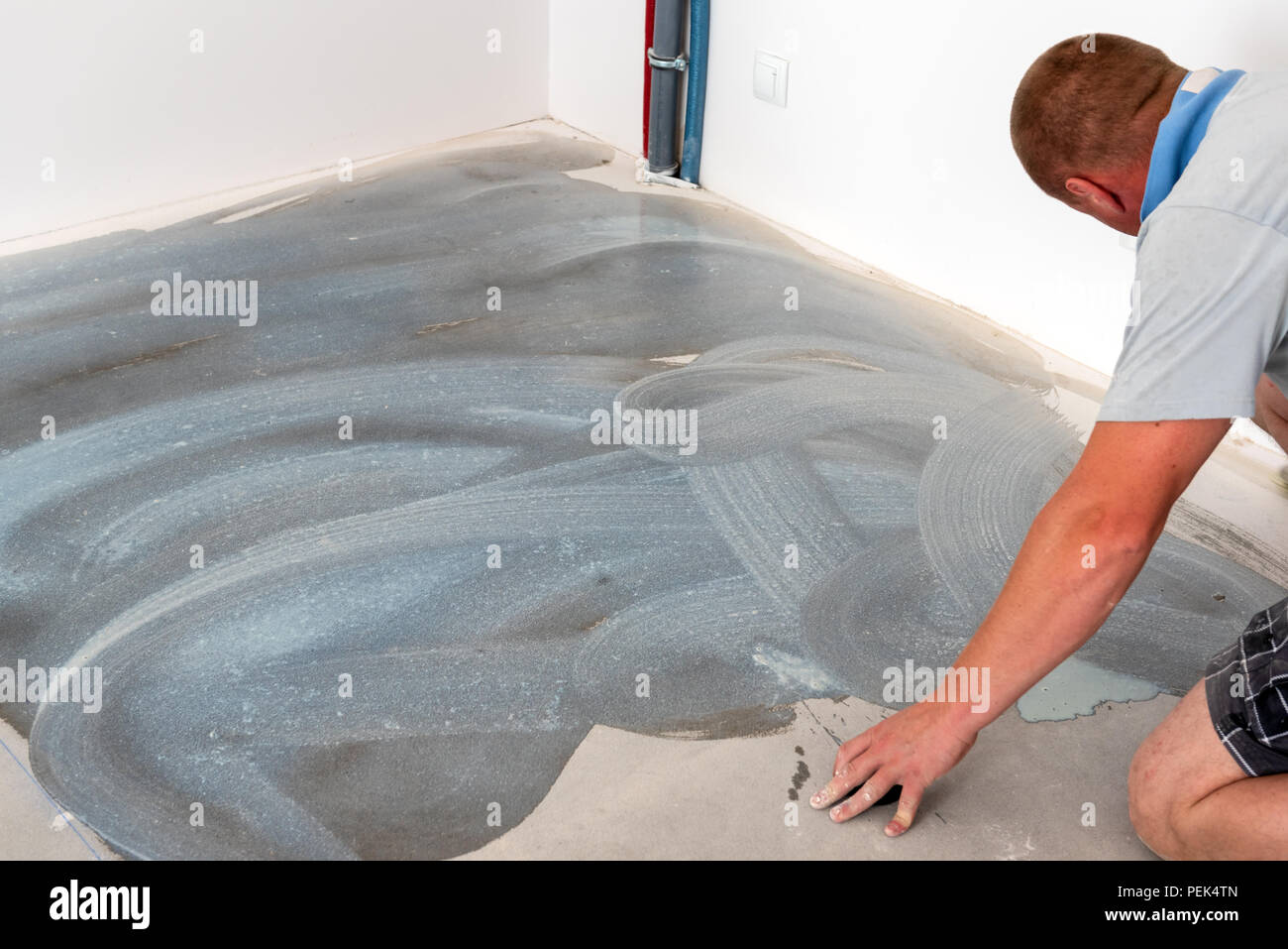 A worker puts the foundation under the ceramic tiles. Home ...