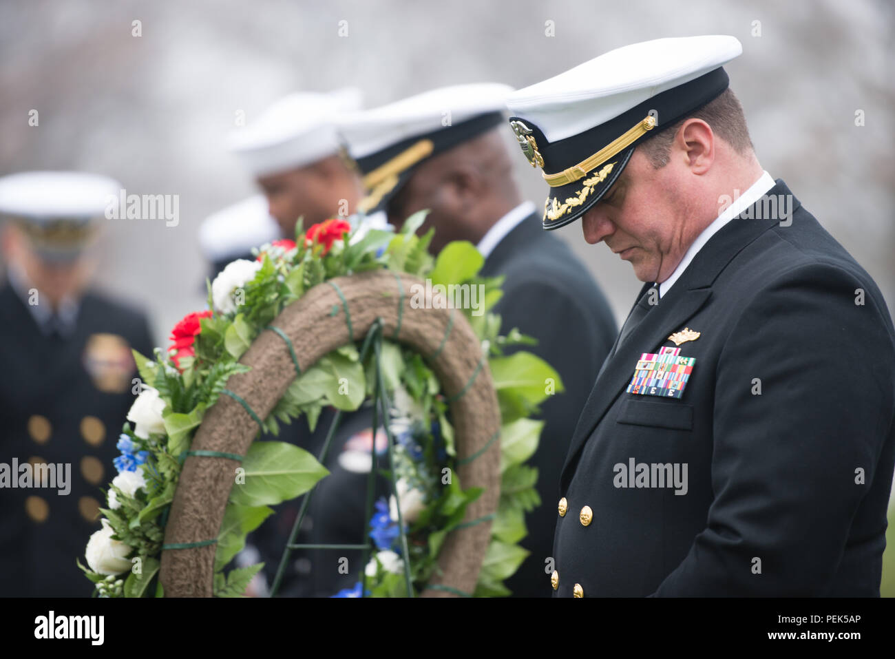 "Cmdr. Joseph Fraser bows his head during a ceremony to honor U.S. Navy Rear Adm. Grace Hopper at Arlington National Cemetery, Dec. 9, 2015, in Arlington, Va. Hopper was a pioneering computer scientist and was nicknamed ""Amazing Grace."" (U.S. Army photo by Rachel Larue/Arlington National Cemetery/released) - Stock Image"