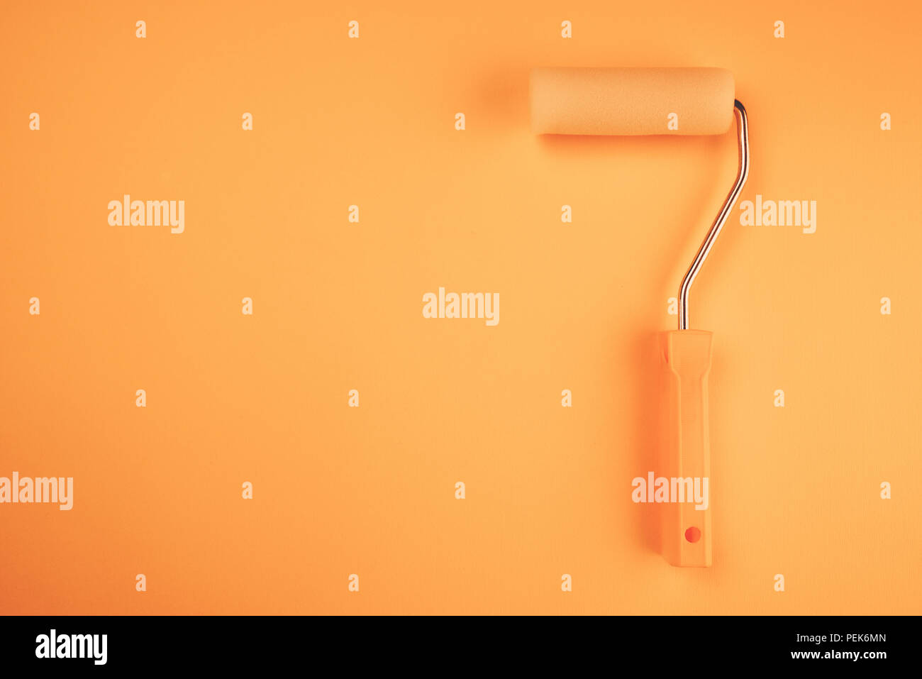 Paint roller for wall painting in vivid warm colors - Stock Image