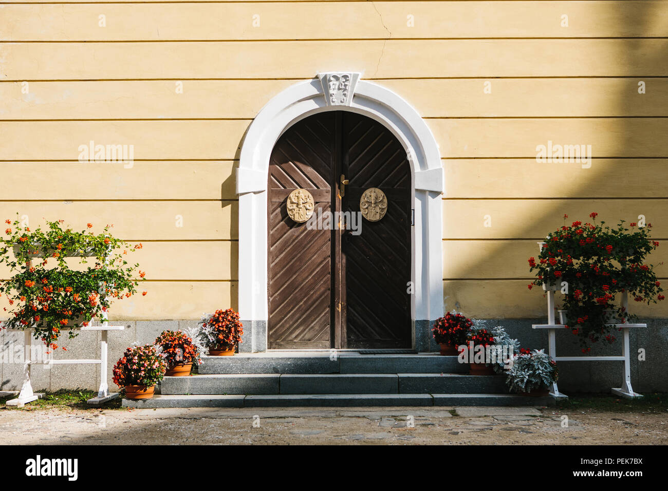 Beautiful arched doors with decorative elements and flower beds in sunny warm day - Stock Image