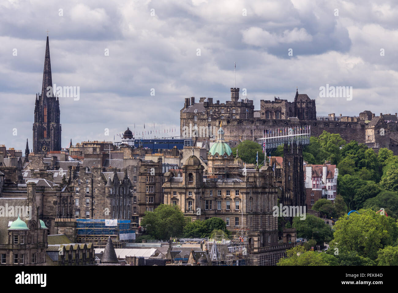 Edinburgh, Scotland, UK - June 13, 2012: Looking from Calton Hill upon dark brown castle and New College buildings under heavy cloudscape. Spire of St - Stock Image