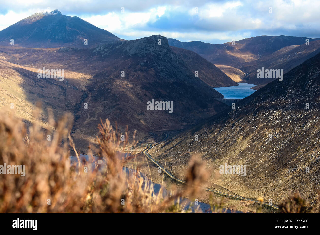 Ben Crom reservoir, dam and Ben Crom Mountain (in shadow). Slieve Bearnagh top left. Silent Valley path (bottom right), Mourne Mountains. - Stock Image