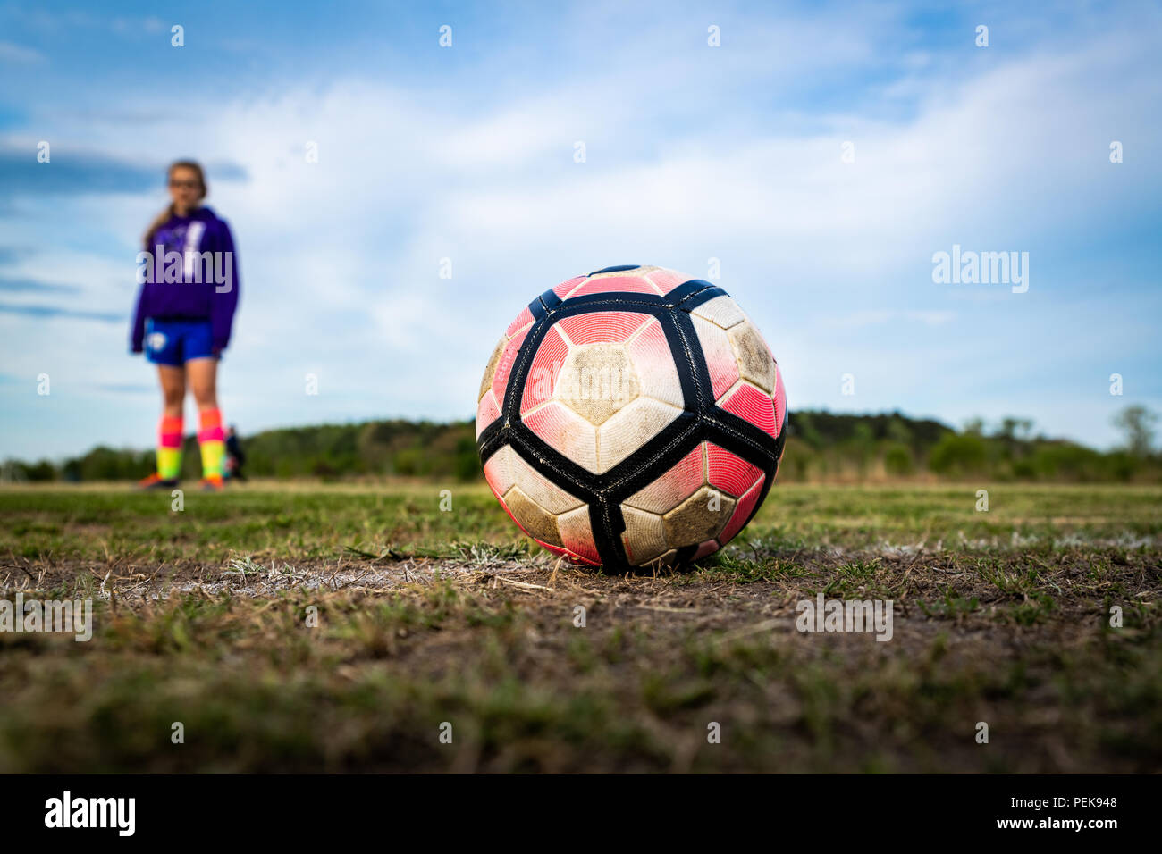 A young girl stands behind a soccer ball, preparing to kick it.  Concepts: youth sports, athlete, focus, preparation, practice, intensity, aspiration, - Stock Image