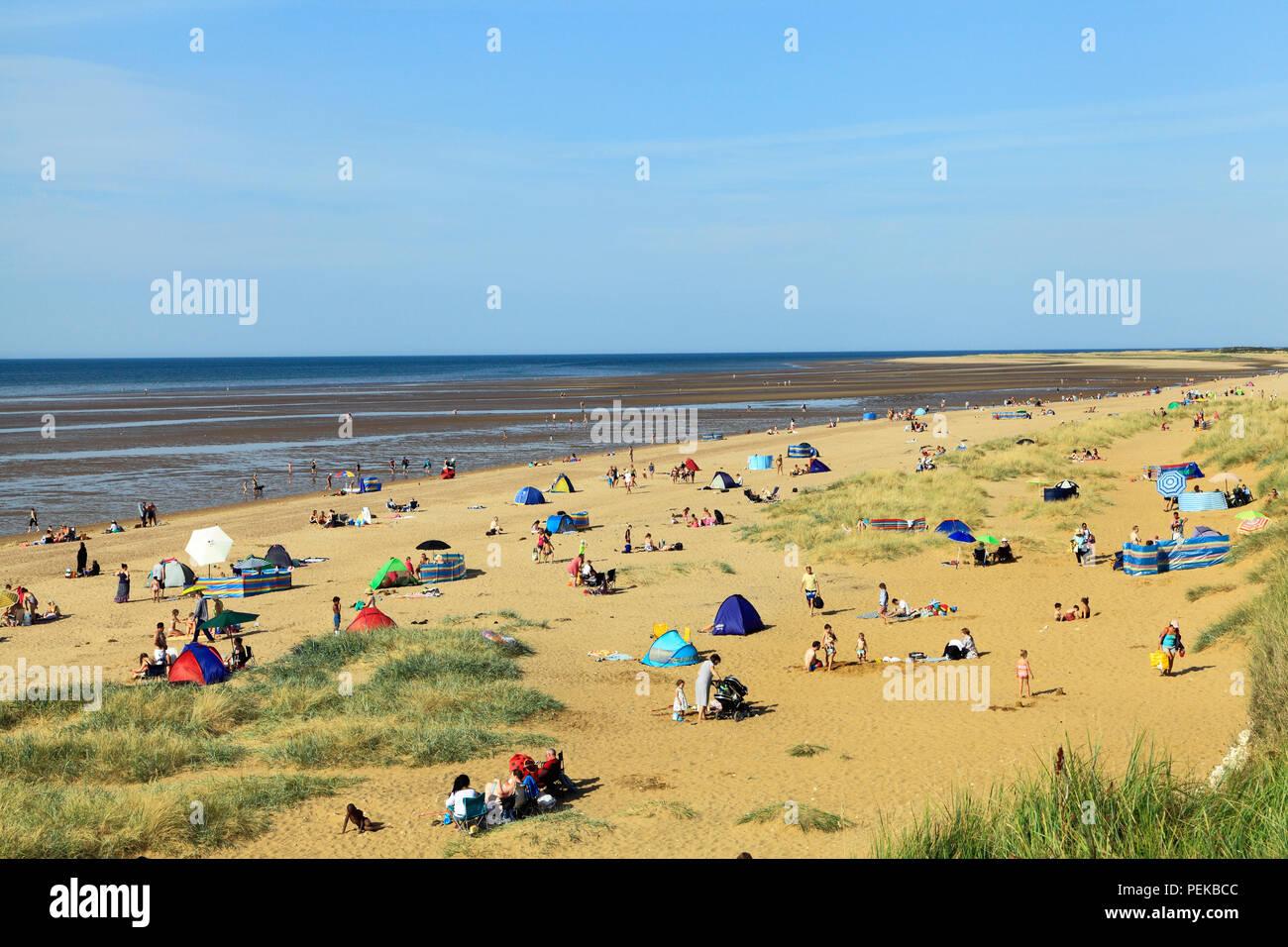Old Hunstanton, beach, sand, bay, sunbathers, sunbeds, North Sea, coast, Norfolk, England, UK - Stock Image