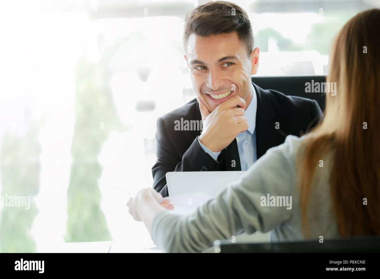 Applying for new job,career opportunity concept : Executive management or recruitment representative interviews applicant for a vacant position,woman submits an application form to an interviewer - Stock Image