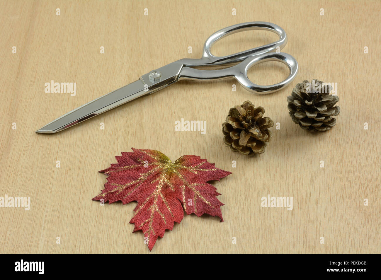 Items for Crafting autumn Thanksgiving decoration with scissors, pine cones and red fabric leaf - Stock Image