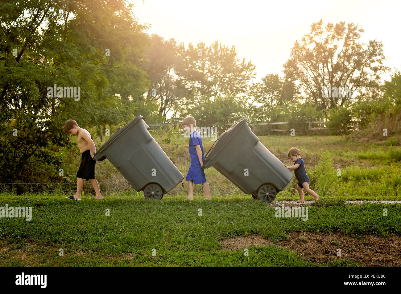 Three young boys taking out the trash bins - Stock Image