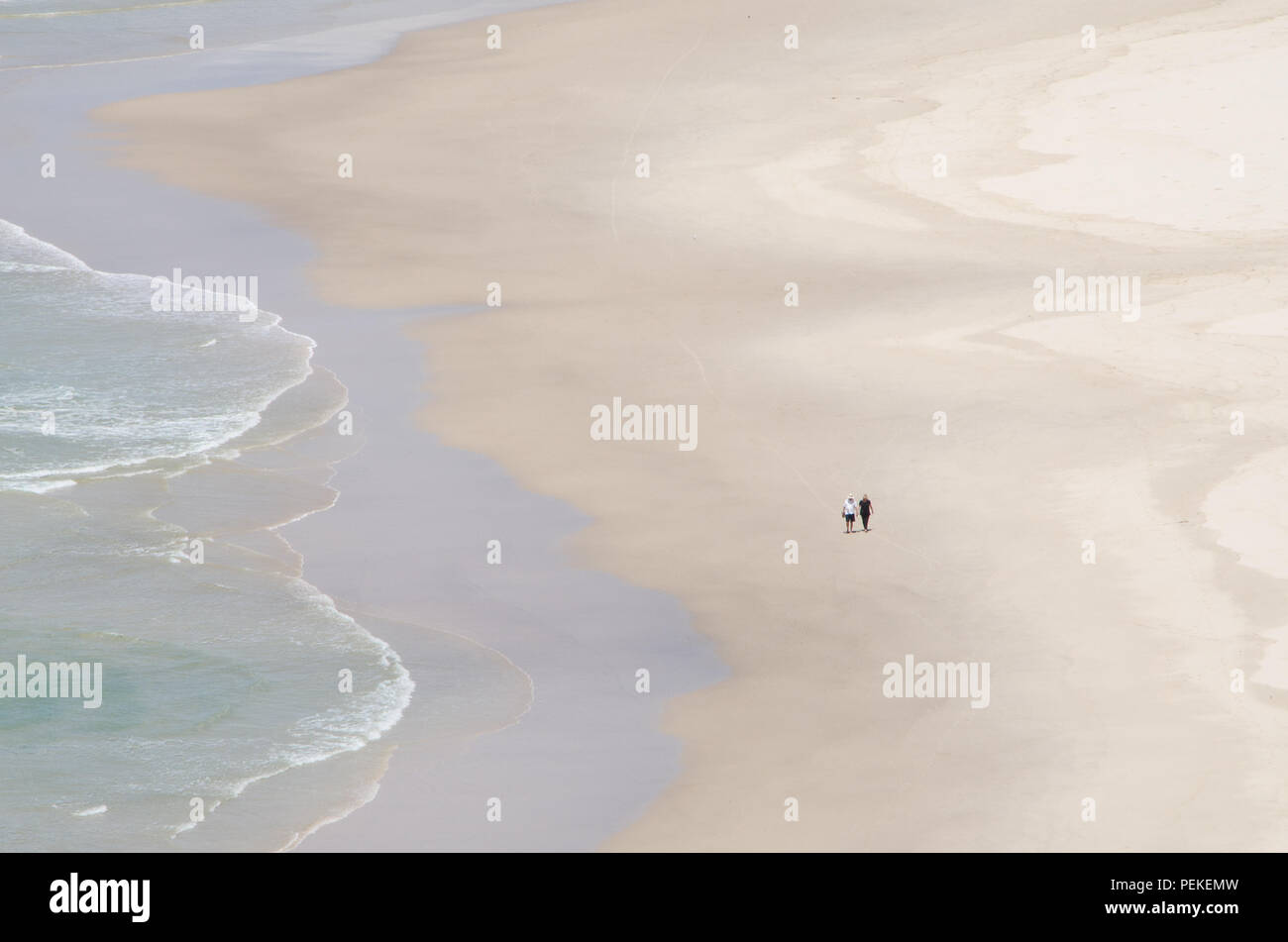 Two people walk along the waters edge on empty beach, Tallow Beach, Byron Bay, New South Wales, Australia. Couples peaceful solitude on lonely beach . - Stock Image