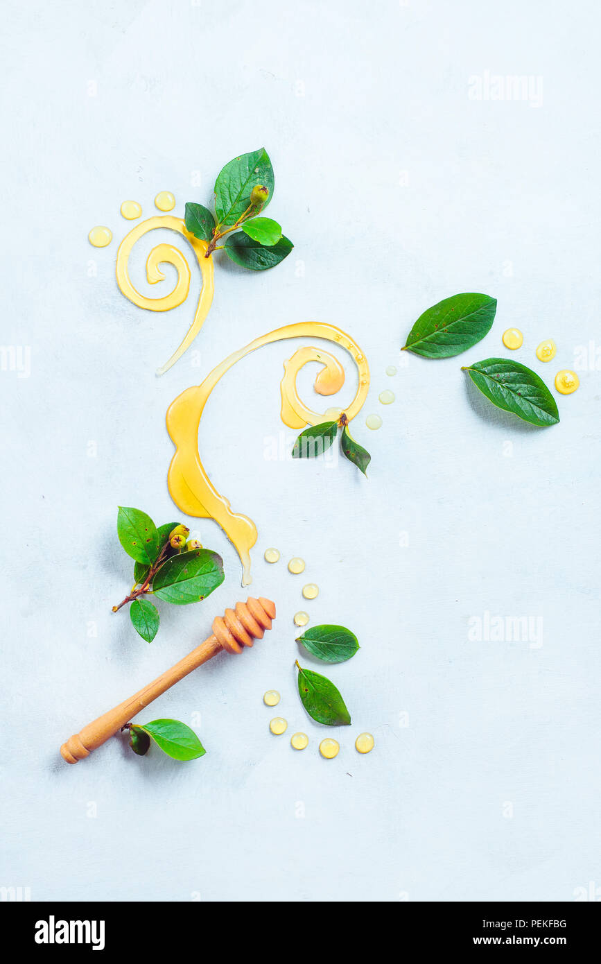 Honey spoon with decorative honey swirls, dots, and green leaves on a white background with copy space. Painting with food concept. Creative food flat - Stock Image