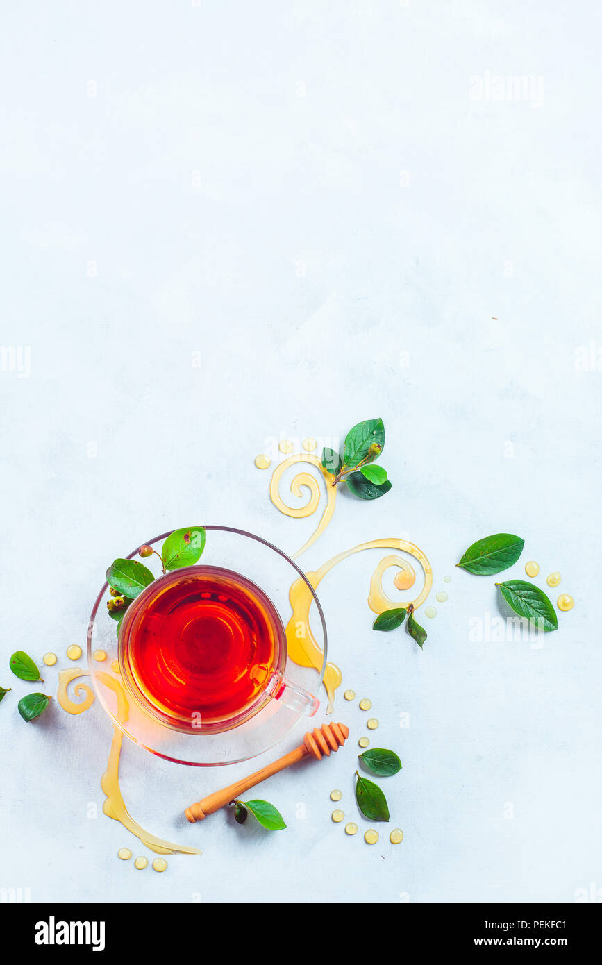 Glass cup of tea with decorative honey swirls and green leaves. Home remedies flat lay on a white background with copy space - Stock Image