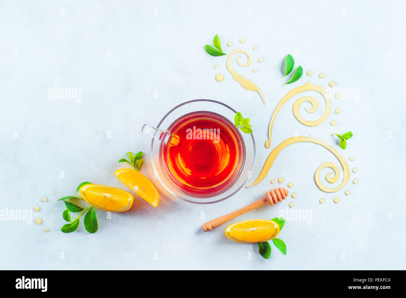 Glass cup of tea with decorative honey swirls, lemon slices and green leaves. Home remedies flat lay on a white background with copy space - Stock Image
