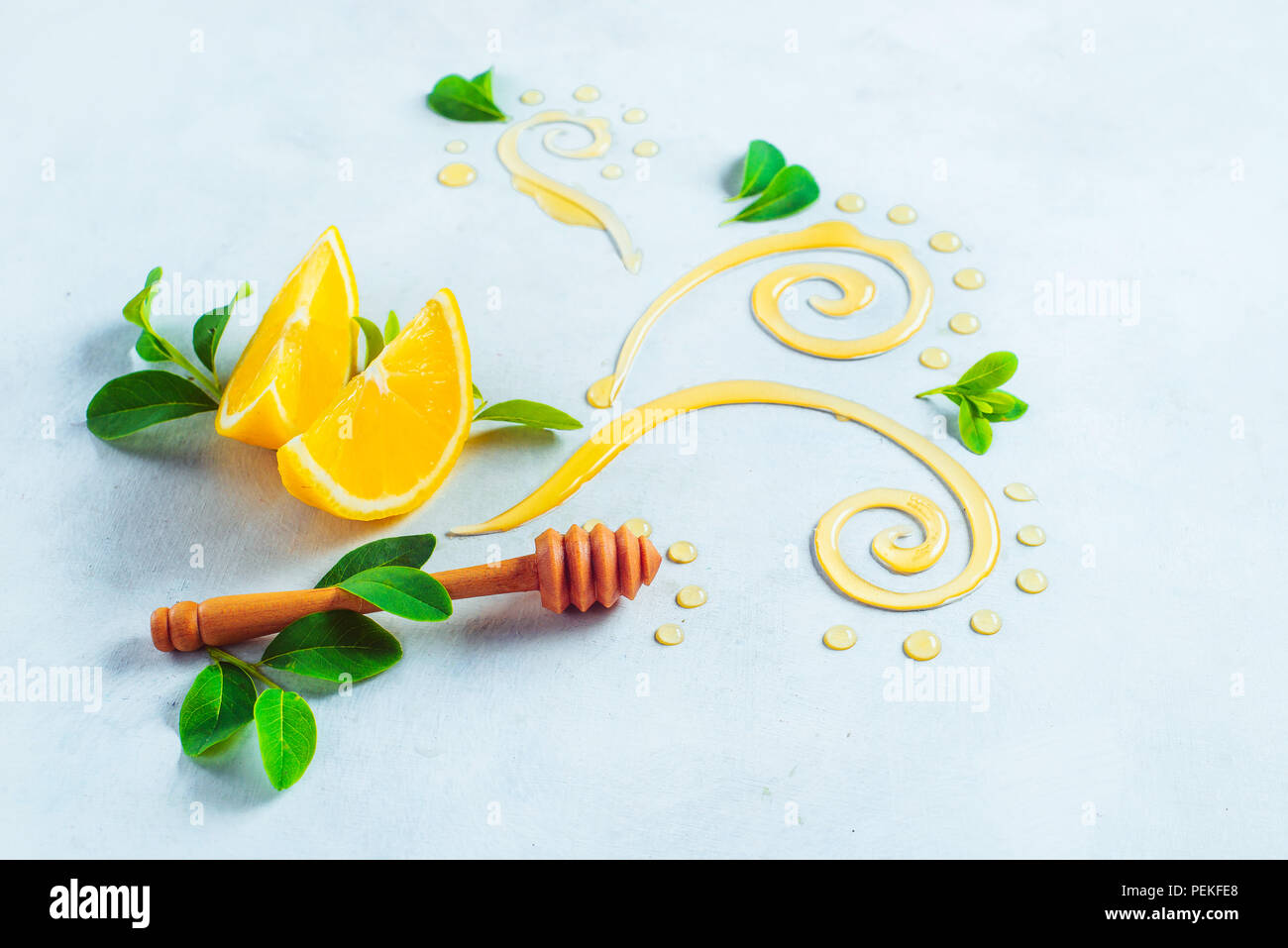Honey dipper with decorative honey swirls and lemon slices on a white wooden background with copy space. Creative food photography. Painting with food - Stock Image