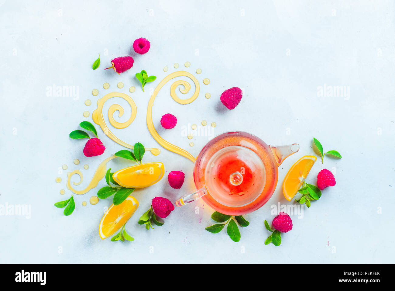Honey and tea header. Glass teapot with decorative honey swirls, lemon slices and green leaves. Home remedies flat lay on a white background with copy - Stock Image