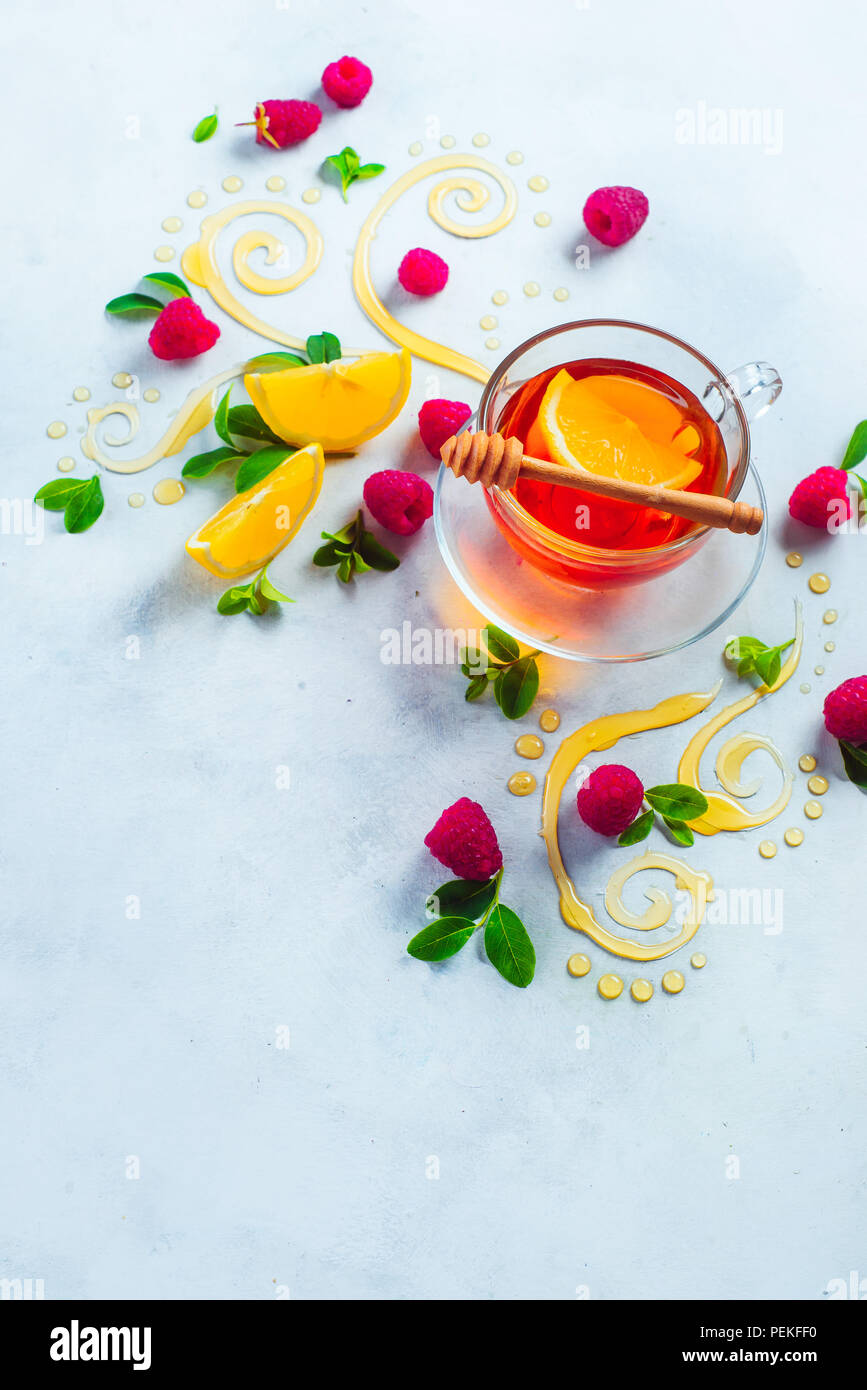 Honey tea from above. Decorative honey swirls, lemon slices, berries and tea in a glass cup on a white wooden background with copy space. Creative food flat lay - Stock Image
