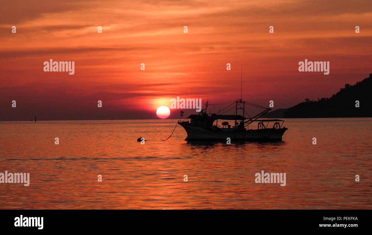 Landscape view of a sunset over the south China sea in Kota Kinabalu (Borneo, Malaysia), with an old fishing boat in the foreground, on the right - Stock Image