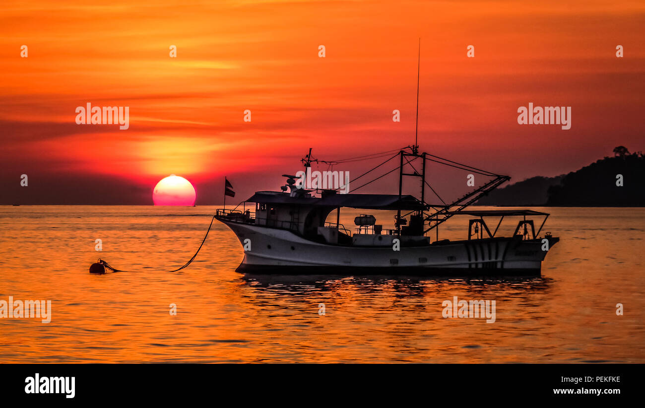 Landscape view of a sunset over the south China sea in Kota Kinabalu (Borneo, Malaysia), with an old fishing boat in the foreground - Stock Image