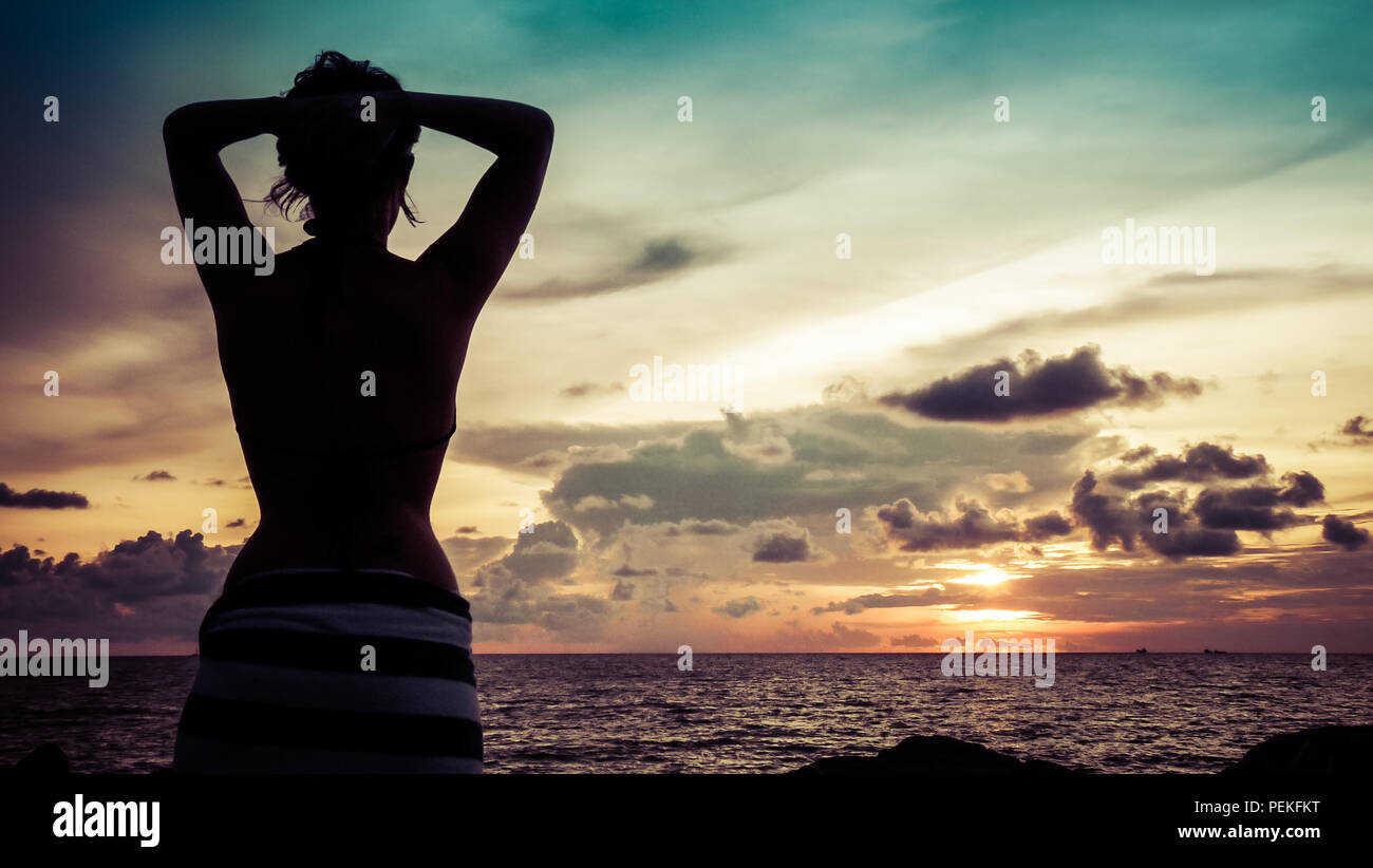 Landscape view of a sunset over the south China sea in Miri, with the silhouette of a beautiful girl in the foreground - Stock Image