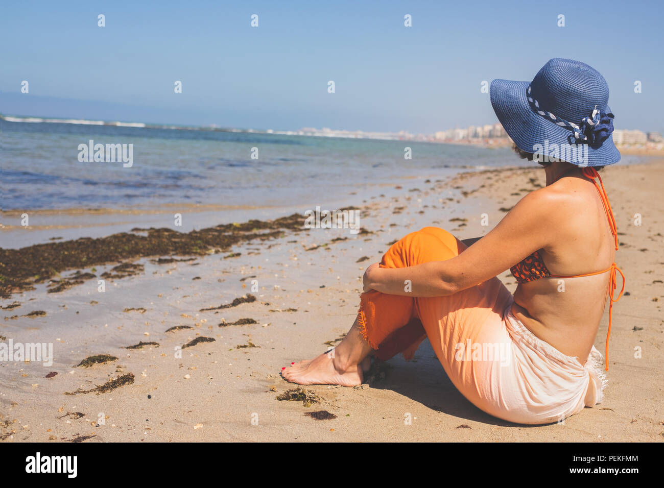 Woman in bikini is on vacation sitting on the beach in summer. - Stock Image