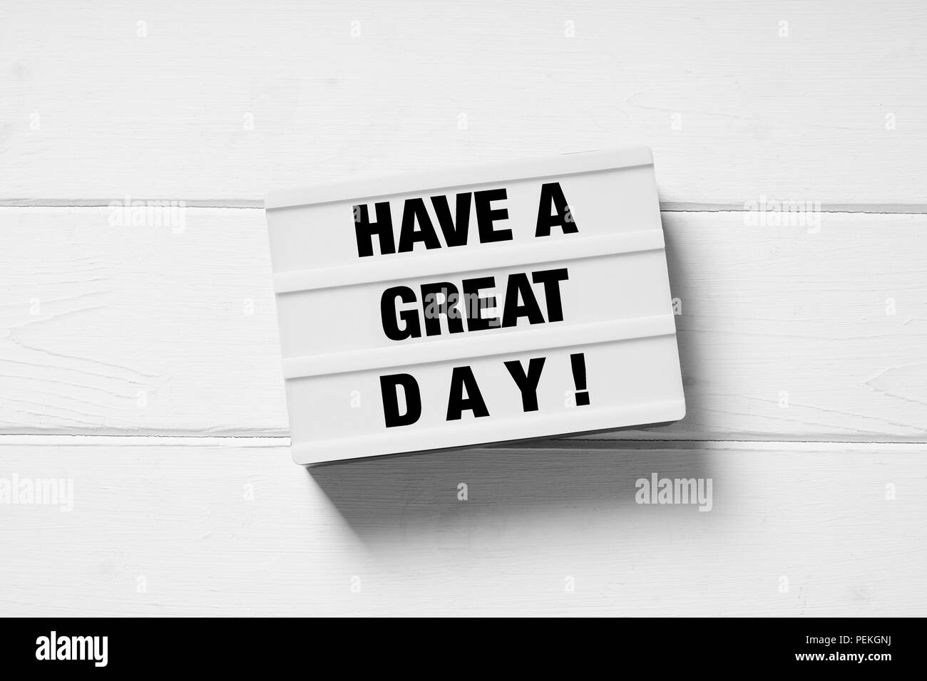 have a great day motivational text on light box light box sign on white wooden background - Stock Image